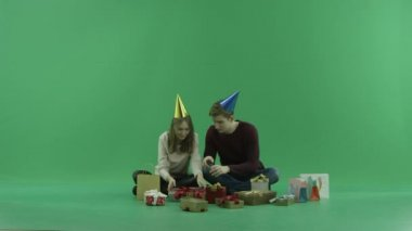Young couple opens a nice Christmas gift, chroma key on background