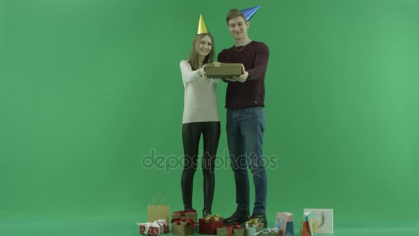 Young couple shows Christmas gift box to the camera, chroma key on background– stock footage