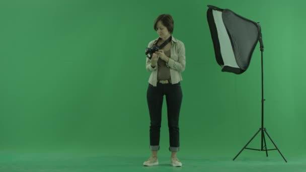 Eine junge Frau kontrolliert Kamera auf dem grünen Bildschirm