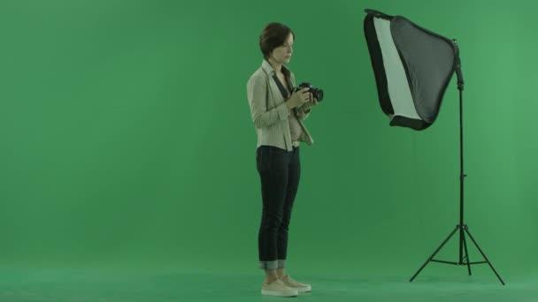 Mladá žena se snaží využít kameru na pravé straně na zelené obrazovce
