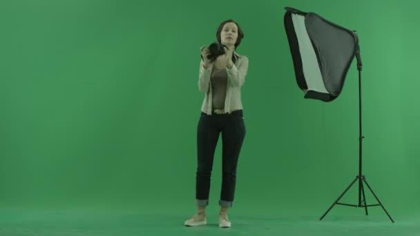 Mladá žena pořizování fotografií pozorovatele na zelené obrazovce a opravit jeho postavení