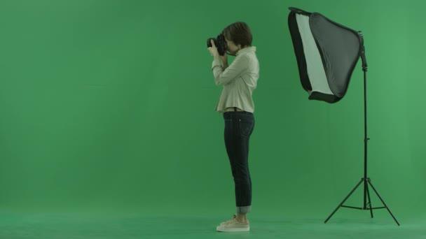eine junge Frau fotografiert auf der linken Seite des grünen Bildschirms und korrigiert die Haltung eines Modells