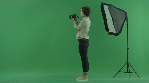 Mladá žena fotografování na levé straně na zelené obrazovce