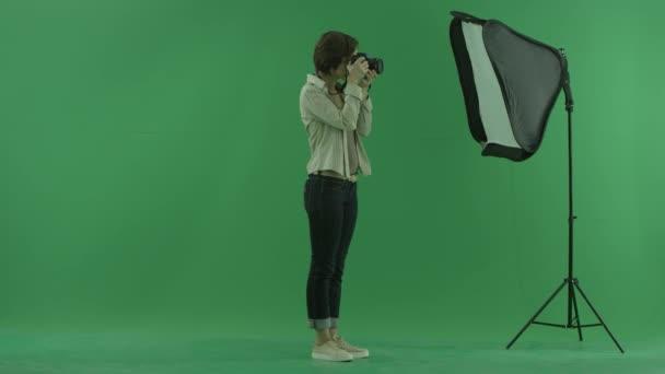eine junge Frau macht Fotos auf der rechten Seite des grünen Bildschirms und korrigiert die Haltung eines Modells