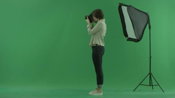 Mladá žena s fotografií na levé straně na zelené obrazovce a opraví postavení modelu
