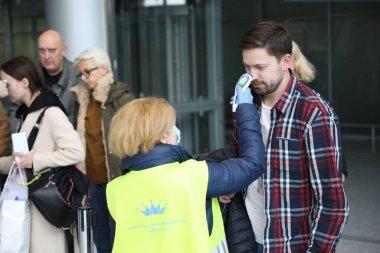 Havaalanı çalışanları ve sınır muhafızları Ukrayna 'nın Lviv kentindeki Danylo Halytskyi Uluslararası Havalimanı' na gelen yolcuların vücut sıcaklıklarını kontrol ediyorlar. SARS-CoV-2 koronavirüsünden kaynaklanan COVID-19 hastalığı