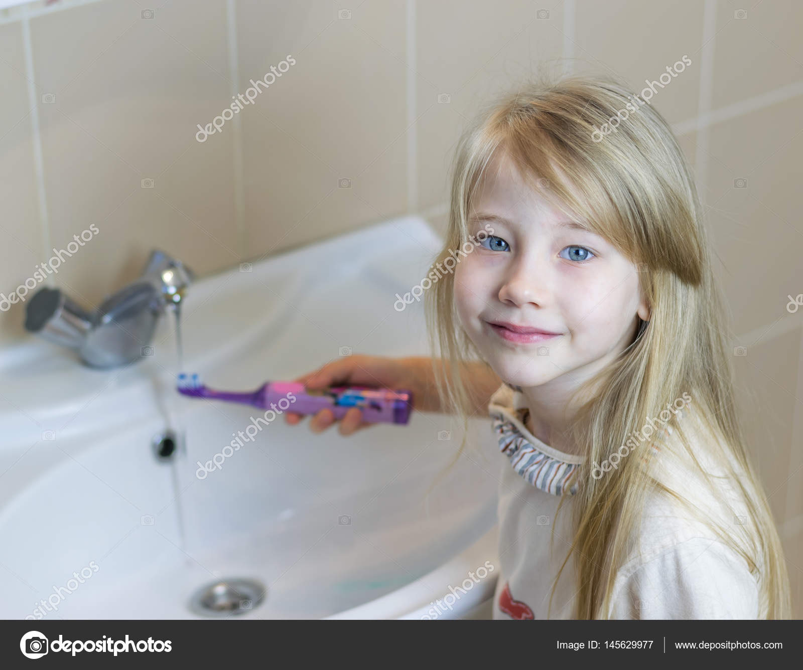 Una niña cepilla los dientes con un cepillo de dientes eléctrico. El  concepto de cuidado oral — Foto de Vladimir75 bac2355c18be