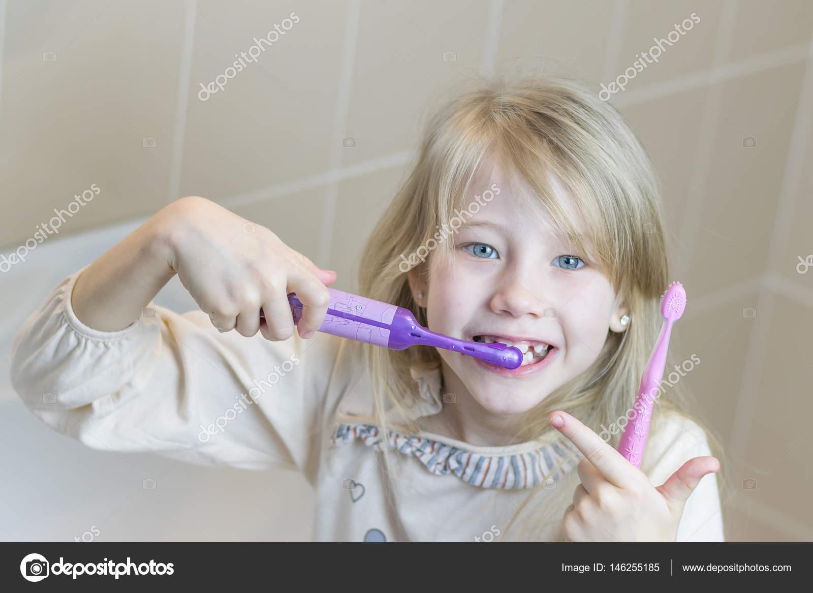 La chica cepilla los dientes con cepillos diferentes dos — Foto de Stock b66a7b24ad8d