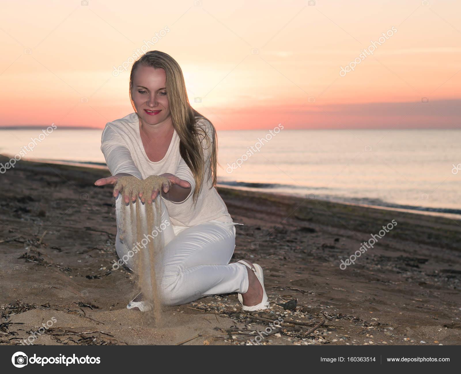 25d92927aeba Donna in vestito bianco gioca con la sabbia al tramonto. Paesaggio di  tramonto in riva al mare con una donna — Foto di ...