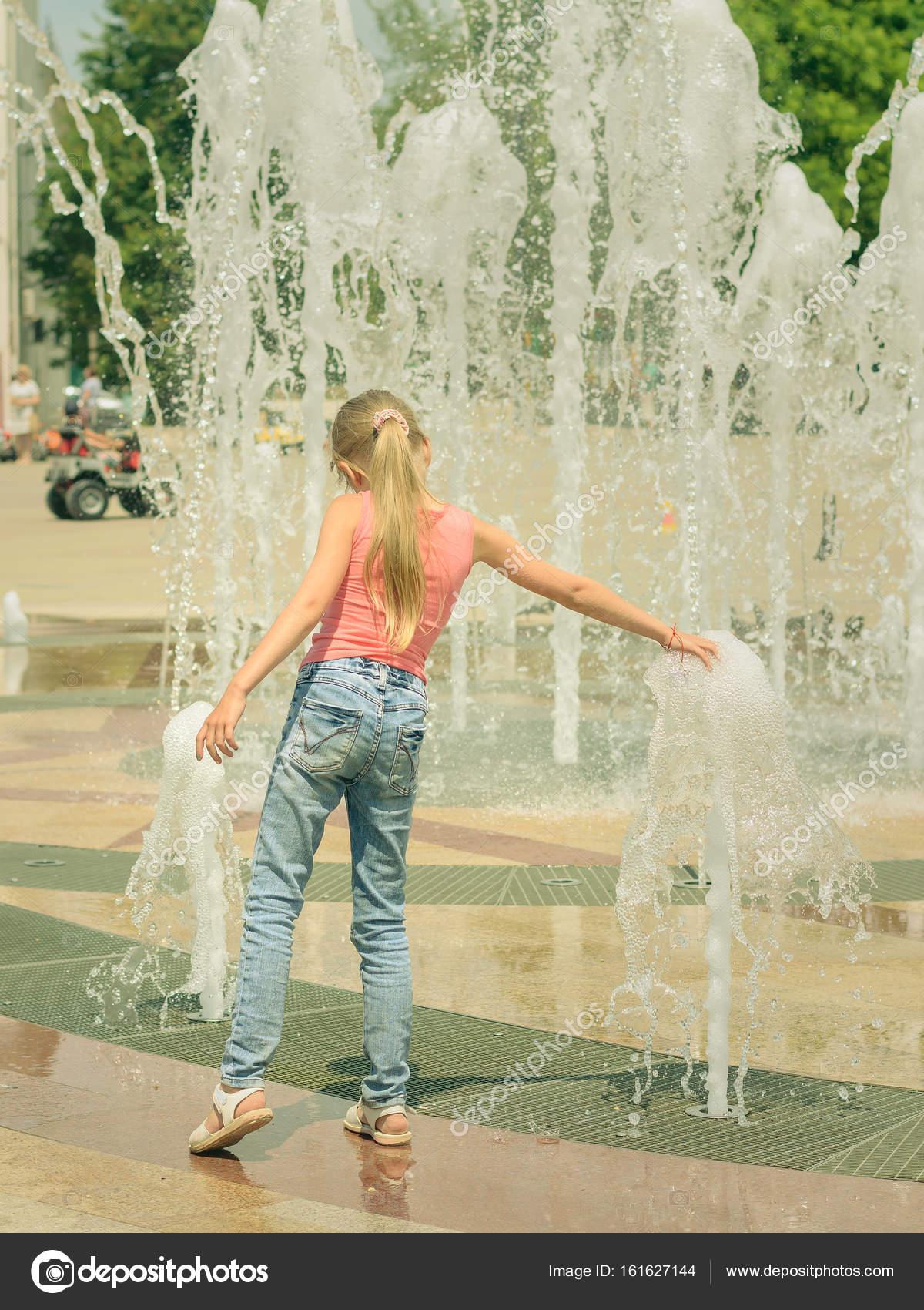 Девушки в джинсах у фонтана