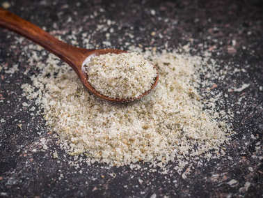 Little brown spoon on a pile of salt with herbs on the stone table.