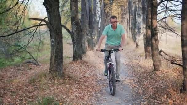 Man cyclist to riding a bicycle in the autumn forest