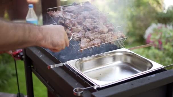 man pulls meat grills, BBQ braizer