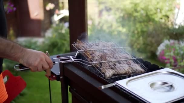 Man grilling pork meat on brazier, flipping pieces.