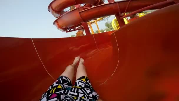 Slope down by water slide in water park. Fun travel inside of the multi color tube at aqua park filmed on action camera.