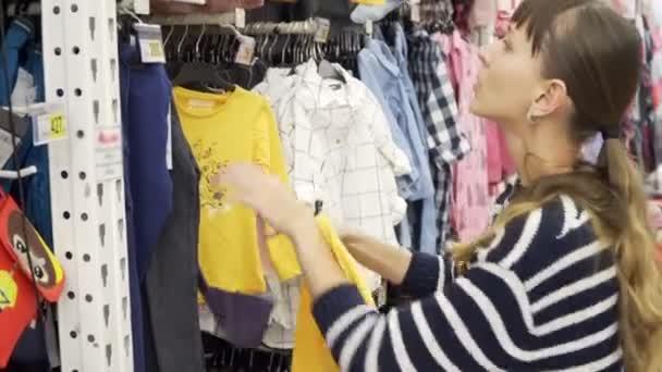 303dca26bf1 Joven madre comprar ropa para niños en una tienda de ropa. Ver artículos.–  metraje de stock