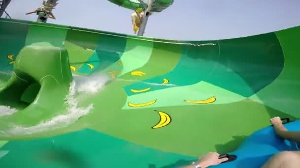 Happy man and woman riding down the water slide. People having fun in water park on resort during summer vacation
