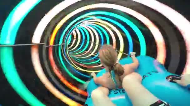 Slope down by water slide in water park. Fun travel inside of the multi color tube at aqua park filmed on action camera. Slow motion.