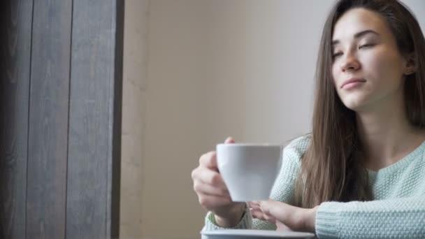 Krásná dívka sedí u stolu a pití čaje. Relaxační