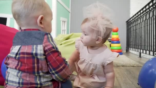 Dvě děti, chlapec a dívka hraje s hračkami na hřišti.