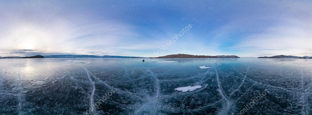 Blue ice of Lake Baikal covered with cracks, cloudy weather at s