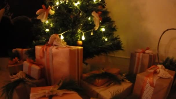 Dárkove boxy pod ozdobený stromeček jedle s hračkami a bílé světlo mrkání garland. Pohyb kamery snímku.