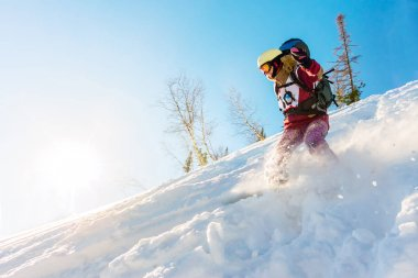 Freerider girl snowboarder slides from the mountain in the light