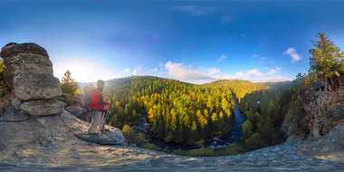 Backpacker on top of a rock fall at dawn. Spherical panorama 360 180 degrees equidistant