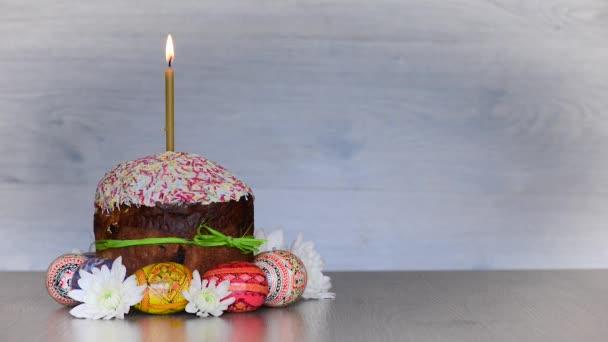 Ostern Kuchen Kulich mit Kerze und Eiern an Frühlingsblumen auf hölzernen Hintergrund