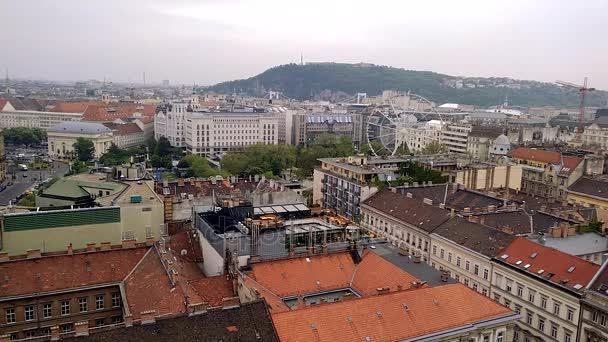 Letecký pohled od Saint Istvan Bazilika na ruské kolo v Budapešti. Střechy domů v historické části Budapešti. Stavební jeřáb rozbaluje boom