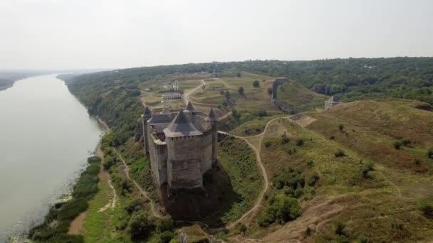 Luftaufnahme der mittelalterlichen Burg von Hotyn auf dem grünen Hügel über dem Fluss.