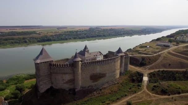 Letecký pohled na středověký hrad Chotyn na zeleném pahorku nad řekou.