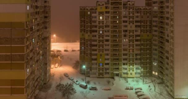 Sněhová bouře v městě. Pohled z okna do dvora v noci. dolů se