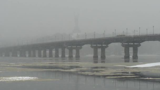 Pohled z mostu Paton v zimě. Sněžení v Kyjevě nedaleko řeky Dněpru.