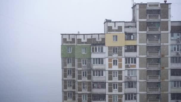 Sněhová bouřka ve městě poblíž budovy na kopci. Detailní záběr.