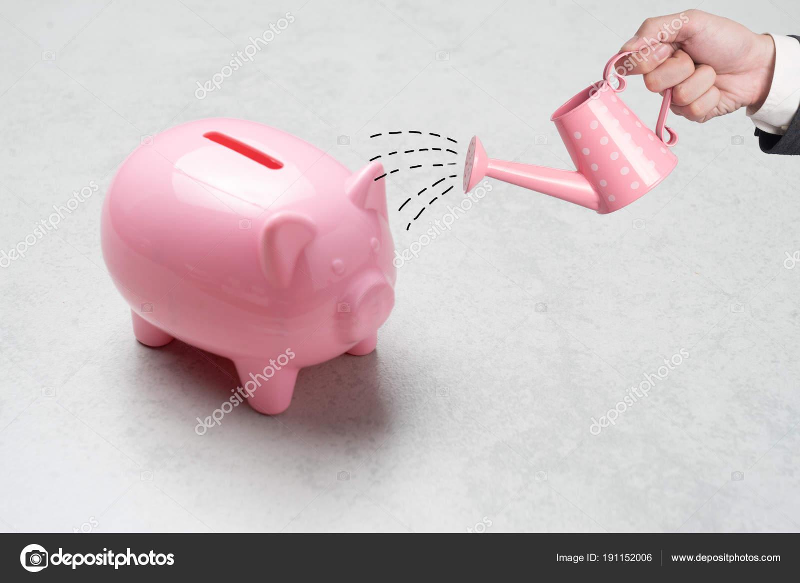 tirelire rose couleur rempli de pièces de monnaie sur fond de béton
