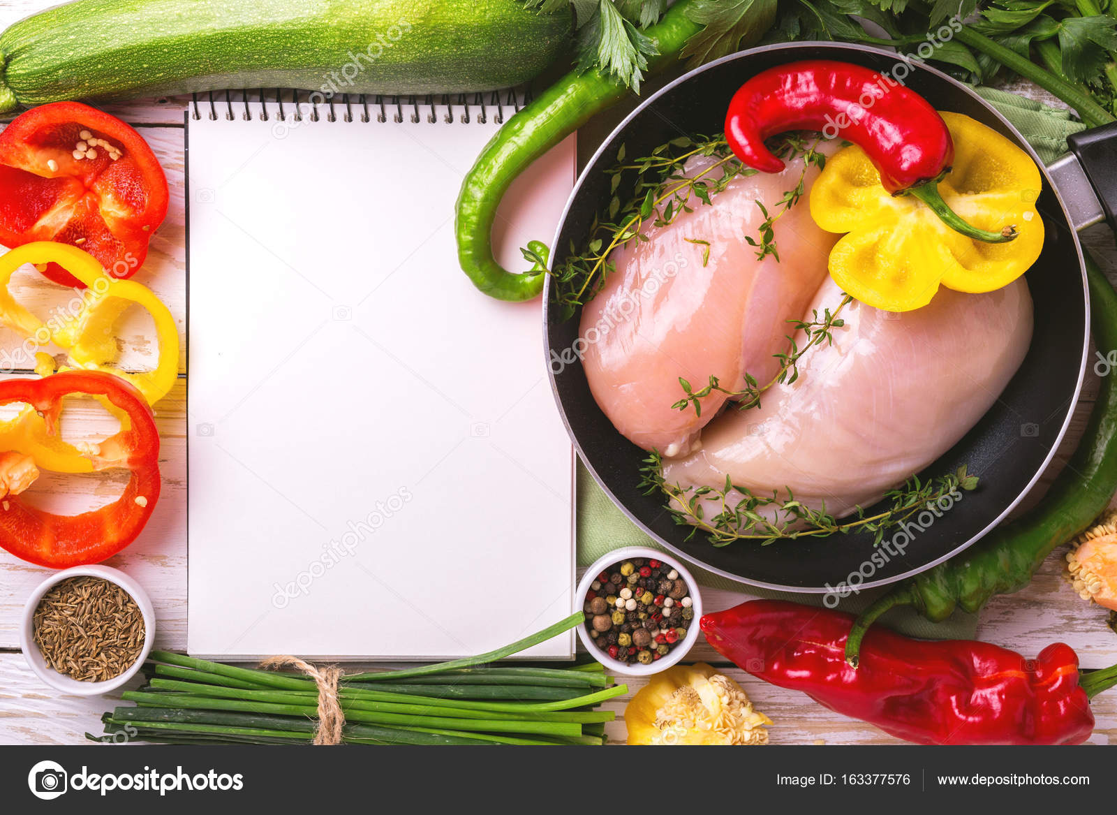 Raw chicken breast fillets with vegetables ingredients in pan raw chicken breast fillets with vegetables ingredients in frying pan around white recipe notebook book for tasty diet top view food cooking ackground with forumfinder Images