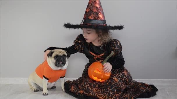 Aranyos lány és az ő kis kutya ruhák öltözött a Halloween. Gyermek egy kép-ból varázsló ül a padlón. Tök - Halloween-szimbólum