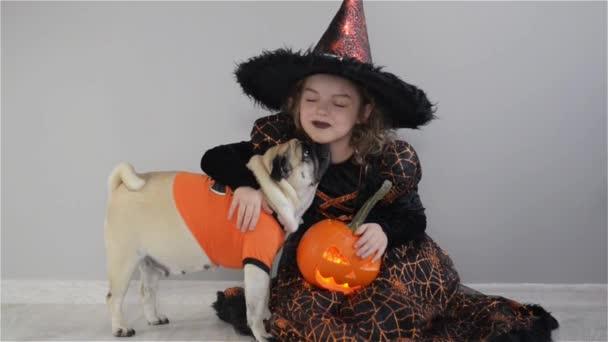 Aranyos lány és az ő kis kutya ruhák öltözött a Halloween. Gyermek egy kép-ból varázsló ül a padlón. Tök - Halloween szimbólum. Lány tartja a sütőtök, és felöleli a mopsz