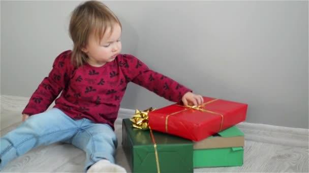 Nettes kleines Mädchen sitzt neben hellen Schachteln und Mädchen packt Geschenke aus. interessiert begutachtet das Baby die Schachteln. Geschenke anlässlich einiger Feiertage. Alles Gute zum Geburtstag. frohe Weihnachten. Frohes neues Jahr