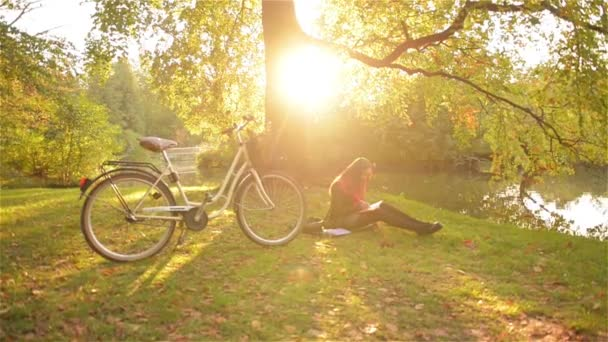 Beautiful caucasian smiling girl sits in the park with her bicycle, student writes in a notebook near a lake, warm autumn day