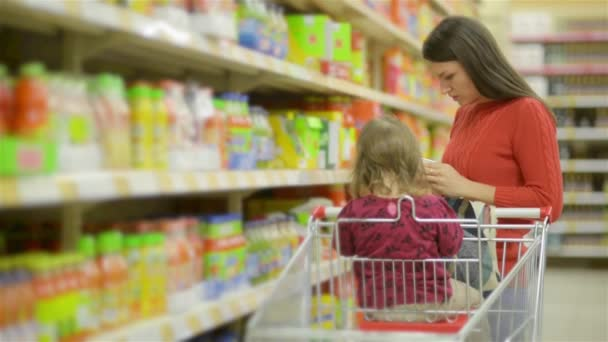 Mother and child walks along wholesale shelves and taking goods in shop trolley, beautiful young wife shopping in a supermarket