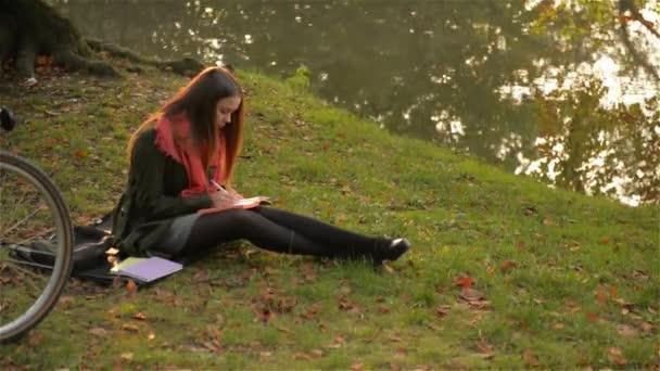 Krásná kavkazské usmívající se dívka sedí v parku s kole, studentka píše v poznámkovém bloku poblíž jezera, teplé podzimní den