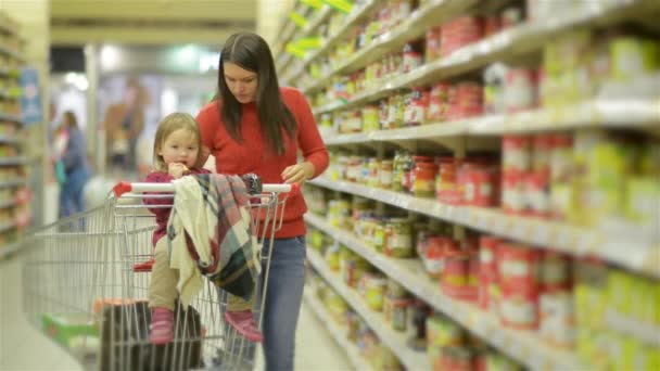 Young Mother and child walks along wholesale shelves and taking goods in shop trolley, woman stands near the supermarket shelf and selects the products for her family