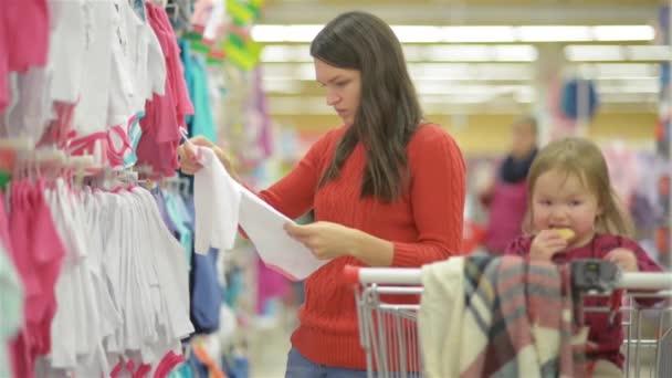 40da9ffdf36f Atractivo joven madre comprar ropa para niños en una tienda de ropa por  menor ver los artículos en una parrilla, hermosa mujer elige ropa de bebé en  la ...