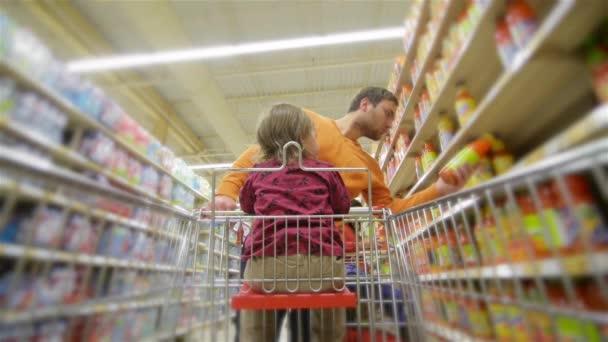 Padre e figlia sorridenti che sceglie i prodotti al supermercato, uomo acquista bevande nellarchivio