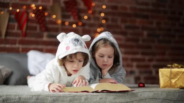 Két kis aranyos testvérek olvasott az ágy mellett Christmas tree fények és a megvilágítás. Boldog család két gyerek