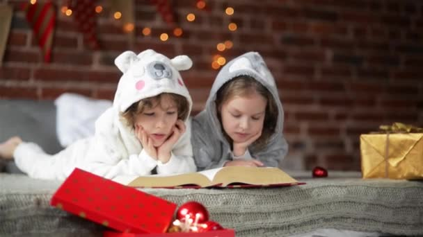 Two Little Cute Siblings Reading A Book In Bed Near Christmas Tree With Lights And Illumination