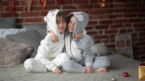 Směje se sourozenci v posteli na Vánoce, bratr a sestra objetí na Štědrý den