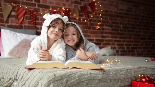 Boldog aranyos gyerek öltözött meleg xmas pizsama nevet és néz a kamerába, mosolygó gyerekek elolvassa a könyvet a karácsony reggel